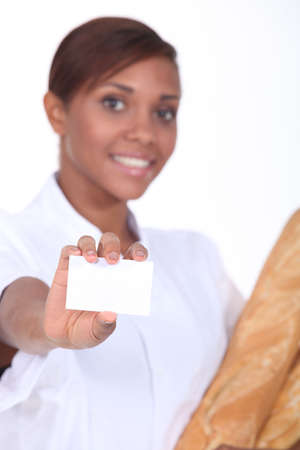 Young female baker with a blank business card Stock Photo - 13713668