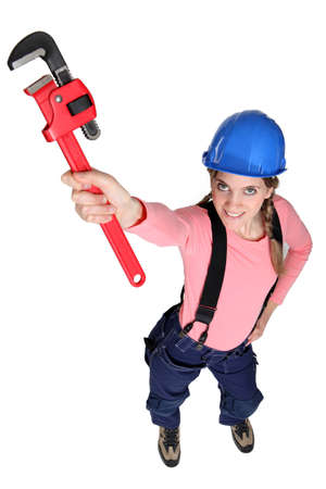workwoman: Tradeswoman holding up a pipe wrench Stock Photo