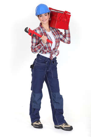 workwoman: Woman holding a toolbox and a pipe wrench