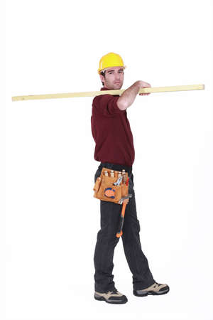 Labourer carrying a wooden plank photo
