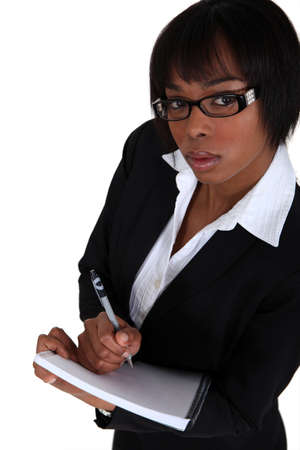 hand holding pen: An African American businesswoman taking notes  Stock Photo