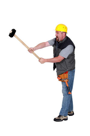 sledge hammer: A construction worker with a sledgehammer