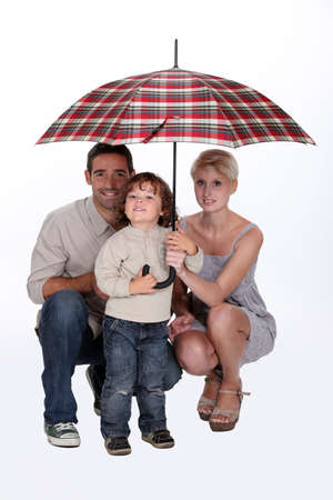 Young family sheltering under an umbrella photo