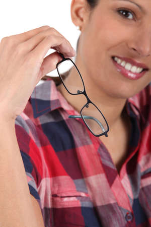 Young woman removing eyeglasses photo