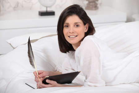 Brunette at home writing in diary photo