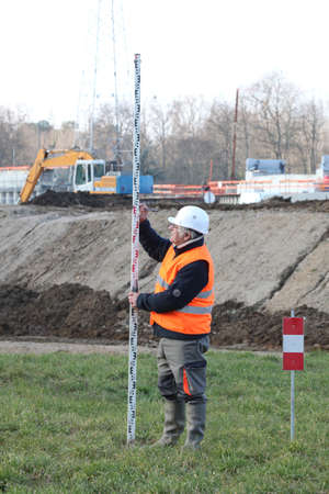 evaluate: Man making taking measurements in construction site