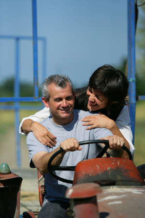 Couple riding tractor photo