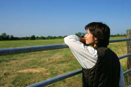 Female farmer stood looking at her land photo