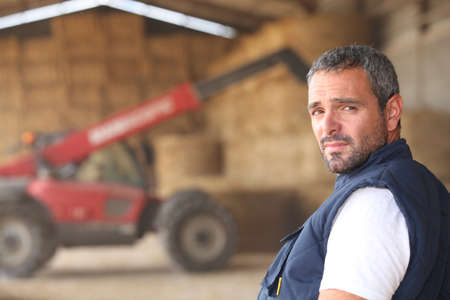 agronomist: farmer posing in front of a tractor