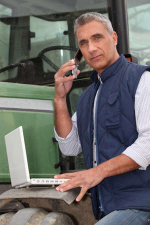 farmer's: Farmer with a laptop and cellphone Stock Photo