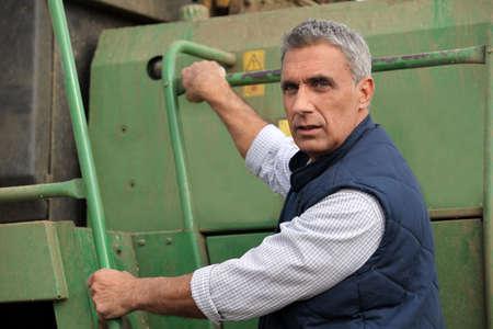 Farmer climbing into a tractor photo
