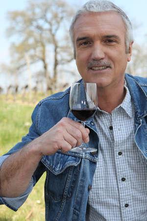 50 to 55 years: Man drinking wine in vineyard Stock Photo