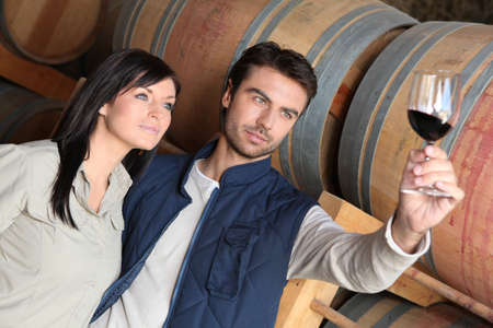 casks: Couple wine tasting in a cellar Stock Photo