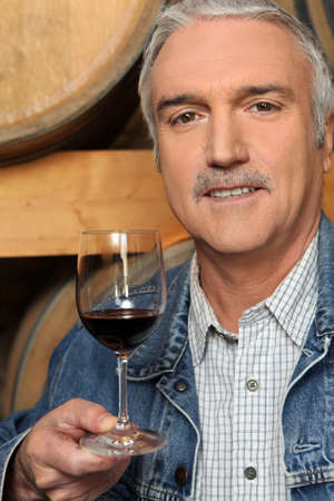 Man tasting a glass of red wine in a vineyard photo