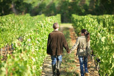 Couple walking in between rows of vines photo