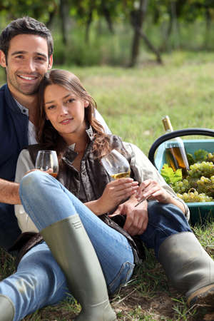Couple with a glass of wine and basket of grapes photo