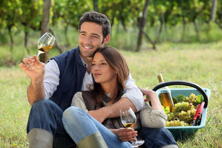 Couple enjoying a bottle of wine whilst harvesting grapes photo