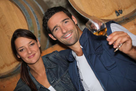 wine tasting: young couple tasting wine in a cellar