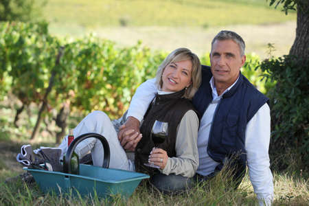 Couple sitting in front of vineyard photo