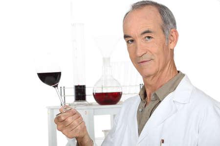tannin: a scientist holding a wine glass in his laboratory