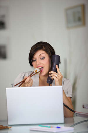 Woman eating sushi while talking on the telephone and looking at her laptop photo