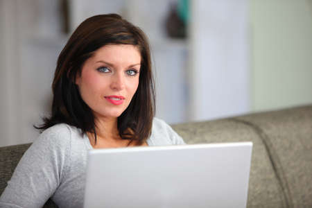 Woman with computer sitting on sofa photo