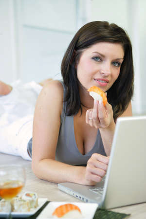 Woman eating sushi working at a laptop photo