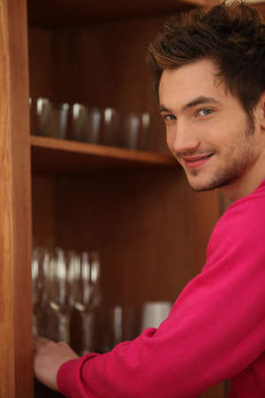 Young man putting glasses away in a cupboard