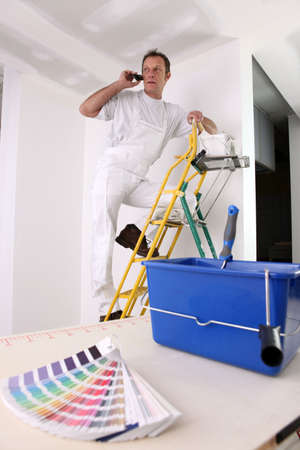 Painter with color swatch making telephone call photo