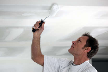 laborious: Man painting his ceiling white Stock Photo