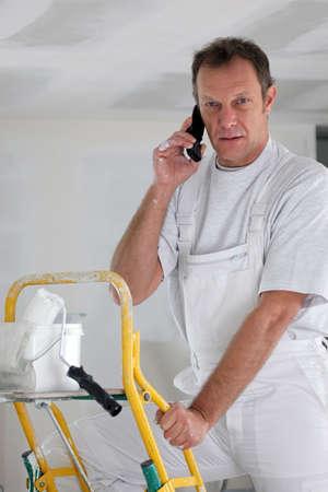answering phone: Pintor contestando al tel�fono mientras se trabaja