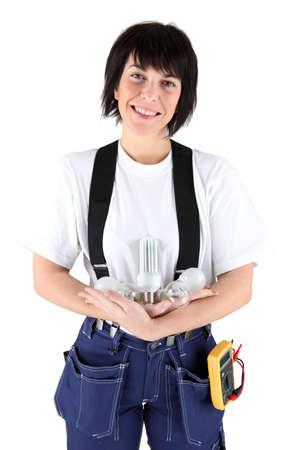 thread count: Female electrician holding light bulbs Stock Photo