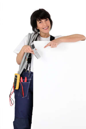 electrician with phone showing white panel photo