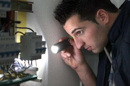 fusebox: Electrician examining a fusebox with a torch