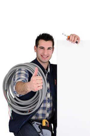 young electrician all smiles carrying hose and board