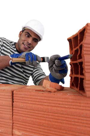 Mason chiseling away at brick photo