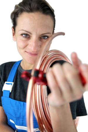koperen leiding: Vrouw loodgieter snijden koperen buis Stockfoto