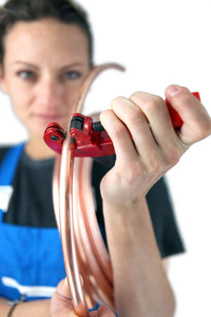 Tradeswoman inserting a copper tube into a clamp photo