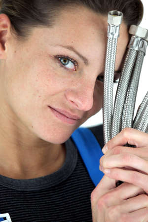Female plumber holding pipes Stock Photo - 13779821
