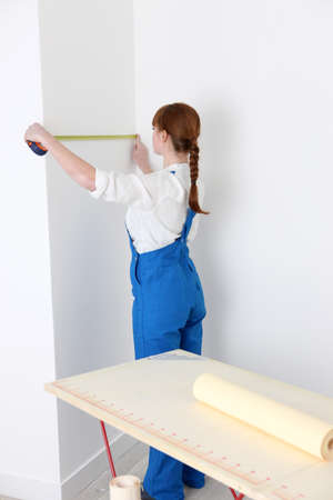 Woman measuring a wall for wallpaper photo