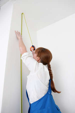 Woman measuring a wall photo