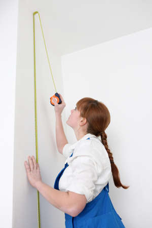 jumpsuit: woman measuring wall