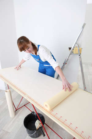 Woman laying wallpaper out on a pasting table Stock Photo - 13778972