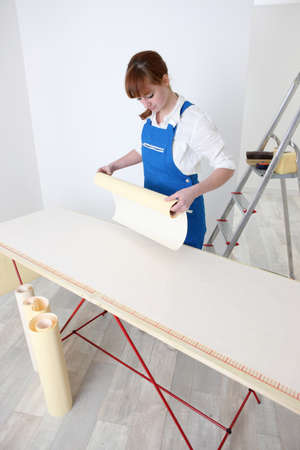 Woman pasting wallpaper photo