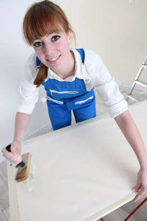 gluing: Woman gluing length of wallpaper