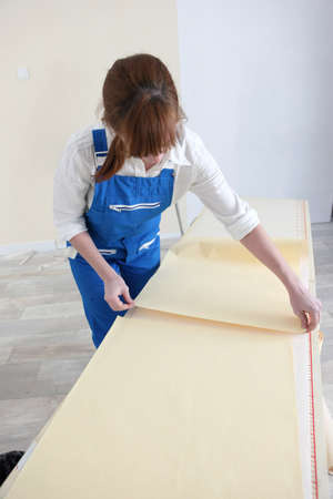 placing: Woman laying out sheets of wallpaper