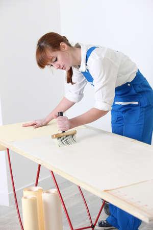 decorator: Female decorator pasting wallpaper
