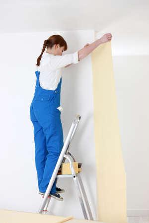woman on ladder laying wallpaper Stock Photo - 13777920