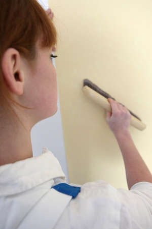 passing over: Woman passing brush over wall paper Stock Photo
