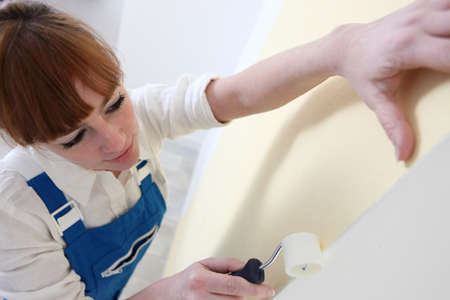 Woman using roller to paste wallpaper to wall photo